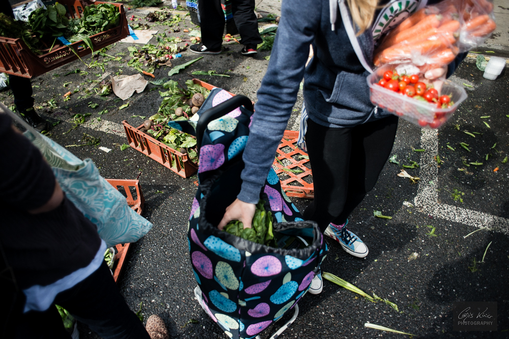 Volunteer from FoodCycle LSE Hub collects surplus food from the farmers' market at Angle, Islington, London